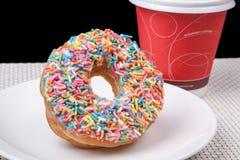 在白色板材和咖啡的五颜六色的多福饼有黑背景 库存照片