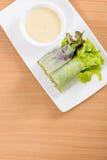 在白色板材和木桌的沙拉卷和奶油沙司 库存图片