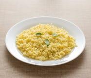 在白色板材和木桌的煮熟的小米谷粒 库存照片