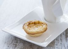 在白色板材和杯子的奶油色蛋糕 免版税库存图片