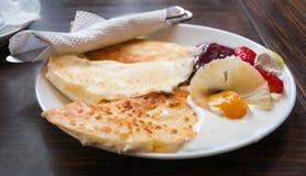 在白色板材和黑暗的背景的薄煎饼与奶油, strawber 免版税库存照片