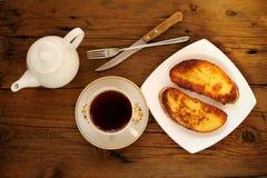 在白色板材的两白色多士有杯子的红茶 库存照片