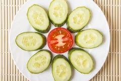 在白色板材的五颜六色的被切的新鲜的有机菜 成熟红色蕃茄和黄瓜以花的形式健康早餐或d的 免版税库存图片