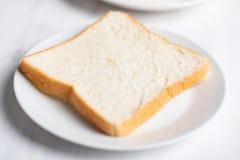 在白色板材的切的面包 免版税库存图片