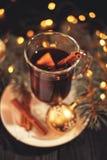 在白色板材的加香料的热葡萄酒在黑木桌,上肉桂条圣诞节球,光 免版税图库摄影