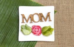 在白色板材的妈妈木文本有在花形状的泰国夹心蛋糕的在绿色香蕉叶子和粗麻布织品背景 图库摄影