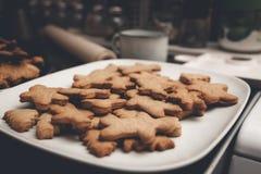 在白色板材的姜饼人曲奇饼 库存图片