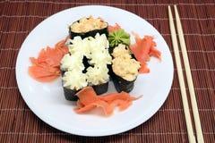 在白色板材的寿司有在柳条秸杆席子特写镜头的筷子的 免版税库存照片