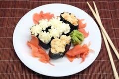 在白色板材的寿司有在柳条秸杆席子特写镜头的筷子的 库存图片