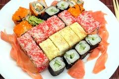 在白色板材的寿司有在柳条秸杆席子特写镜头的筷子的 免版税库存图片