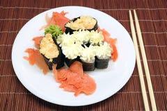在白色板材的寿司有在柳条秸杆席子特写镜头的筷子的 库存照片