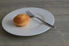 在白色板材的小蛋糕有在木桌上的叉子的 免版税库存照片