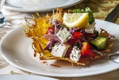 在白色板材的希腊沙拉口味乳酪盘子 免版税库存照片