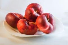 在白色板材的平的桃子 免版税库存照片