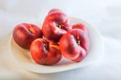 在白色板材的平的桃子 免版税库存图片