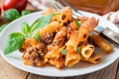 在白色板材的意大利通心面博洛涅塞,面团砂锅用肉末,西红柿酱和乳酪,水平 库存照片
