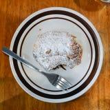 在白色板材的新鲜的新月形面包用搽粉的糖 免版税库存图片