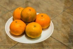 在白色板材的新鲜的橘子在玻璃和陶瓷背景,柑橘reticulata 库存照片