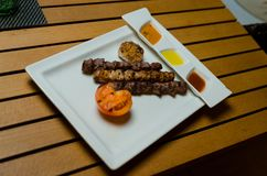 在白色板材的烤羊羔烤肉串有服务板的,辣西红柿酱,草本,在白色木背景 免版税库存图片