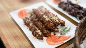 在白色板材的烤肉串有菜的 在串的热的肉 烹调在煤炭的肉 浅的重点 库存照片