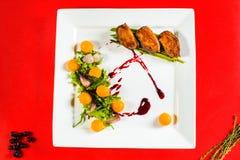 在白色板材的熏制的鸭胸脯内圆角在红色烹饪委员会 免版税库存照片
