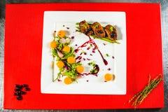 在白色板材的熏制的鸭胸脯内圆角在红色烹饪委员会 库存照片