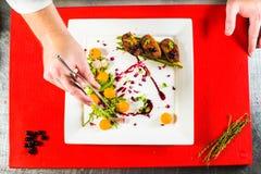 在白色板材的熏制的鸭胸脯内圆角在红色烹饪委员会 免版税图库摄影