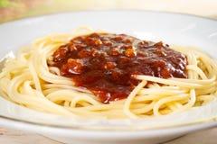在白色板材的特写镜头spaghtti红色调味汁 烹调意大利语的食品成分 库存图片
