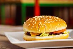 在白色板材的特写镜头新鲜的乳酪汉堡在被弄脏的背景 免版税库存图片