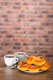 在白色板材的番红花小圆面包有两杯咖啡的 图库摄影