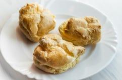 在白色板材的自创被烘烤的奶油饼在轻的木ta 免版税库存照片