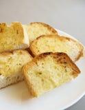 在白色板材的蒜味面包切片 免版税库存照片
