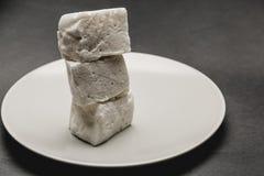 在白色板材的蛋白软糖立方体 免版税库存照片