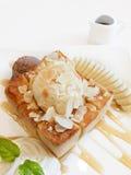 在白色板材的蜂蜜多士用巧克力和vanila冰淇凌 库存图片