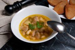 在白色板材的豆汤有金属匙子的,数在丝毫敬酒 免版税库存照片