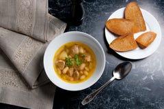在白色板材的豆汤有金属匙子的,数在丝毫敬酒 免版税库存图片