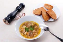 在白色板材的豆汤有金属匙子的,数在丝毫敬酒 图库摄影