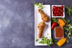 在白色板材的酥脆肯塔基炸鸡腿用蕃茄和调味汁胡椒和绿叶在灰色背景 免版税库存照片