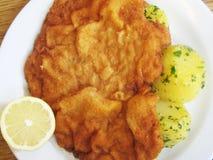 在白色板材的面包weiner炸肉排用土豆和柠檬 免版税库存照片
