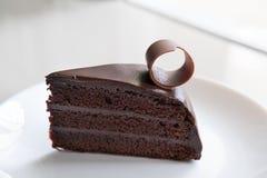 在白色板材的鲜美黑暗的巧克力蛋糕 切的可口可可粉 免版税库存图片