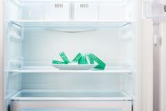 在白色板材的绿色测量的磁带在开放空的冰箱 免版税图库摄影