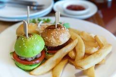 在白色板材设置的微型汉堡 免版税库存照片