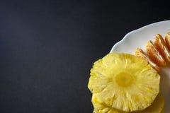在白色板材isola安置的橘子和菠萝切片 免版税库存照片