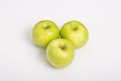 在白色柜台的三个格兰尼史密斯苹果苹果 图库摄影
