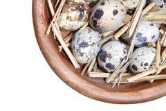 在白色查出的一个木碗的鹌鹑蛋和秸杆 免版税库存图片