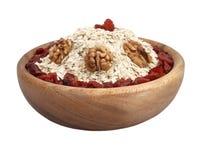 在白色查出的一碗与wallnuts的燕麦和浆果 免版税图库摄影