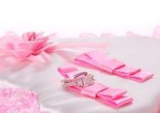 在白色查出的桃红色弓的婚戒 免版税库存图片