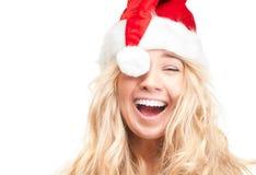 在白色查出的红色圣诞老人帽子的愉快的女孩。 库存图片