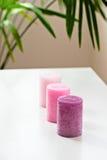 在白色桌上的三个桃红色ombre有气味的蜡烛 免版税图库摄影