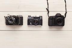 在白色桌上的三台不同照相机 免版税库存图片